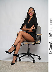 Attractive young Asian business woman sitting on the office chair over light gray wall