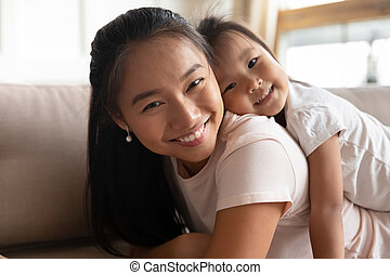 Attractive young asian mother holding on back cute small kid.