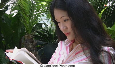 An attractive young asian woman reads a book, in a greenhouse.