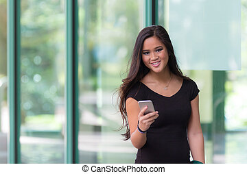Attractive young asian woman smiles at camera while texting on a smart phone