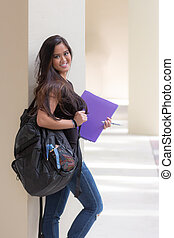 Attractive young asian woman student with backpack and binder on school campus