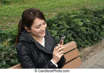Attractive young Asian woman using smartphone