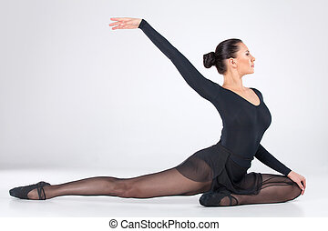 attractive young ballet dancer dancing. elegant female sitting on floor and stretching
