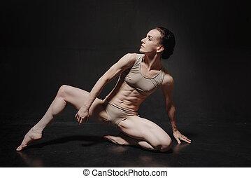 Attractive young ballet dancer dancing in the studio