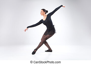 attractive young ballet dancer on white. beautiful ballet dancer practicing and smiling