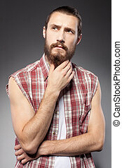 Attractive young bearded hipster guy is pensive