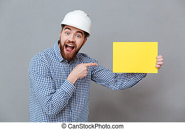 Attractive young bearded man builder holding copyspace blank