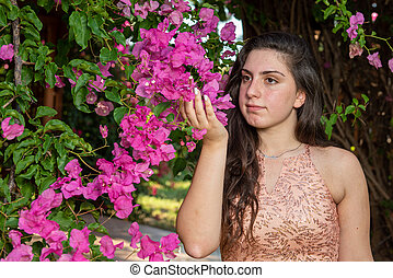 Attractive young beautiful lady, enjoying the pink blooming flowers. Concept of welcoming Spring