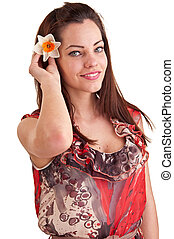 Attractive young beautiful woman smiles and puts a daffodil in her hair on white background