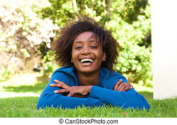 Attractive young black woman lying on grass laughing