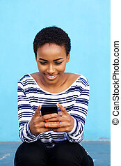 attractive young black woman sitting with cell phone -...