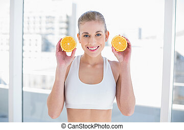 Attractive young blonde model holding two halves of an orange