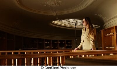 Attractive young blonde woman in glasses posing in the old vintage library on a warm pale light