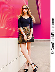 Attractive young blonde woman in leopard skirt, sunglasses with handbag clutch on city street over colorful pink wall background