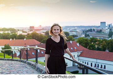 Attractive young blonde woman in the city at sunset