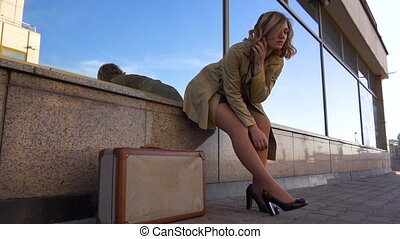 Attractive Young Blonde Woman in Trench with Vintage Suitcase on the Marine Station