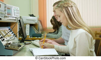 Attractive young blonde woman is studying at university as an engineer. Together with the young man write down the readings on laboratory work.