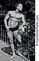 Attractive young bodybuilder smiling, outdoors, showing muscular body