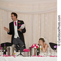 Attractive young bride grimaces at groom's speech during real wedding reception