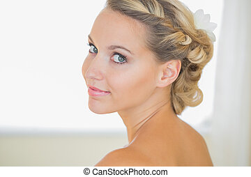 Attractive young bride looking over shoulder smiling at...