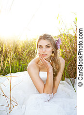 Attractive Young Bride Sitting in the Grass