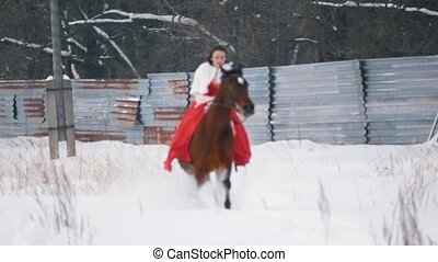 Attractive young brunette in a red dress galloping on a...
