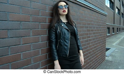 attractive young brunette in black clothes and sunglasses stands near a wall and posing one camera