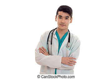 attractive young brunette male doctor with stethoscope in uniform looking at the camera isolated on white background