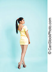 attractive young brunette woman in yellow dress on blue background.