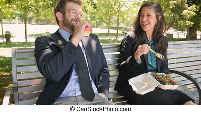 Attractive young business couple eating healthy food outside in 4k