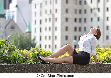 Attractive young business woman relaxes in the city