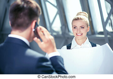 Attractive young businessman and his female assistant are working
