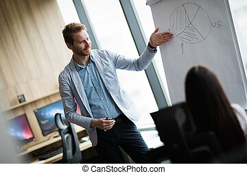 Attractive young businessman doing presentation in office