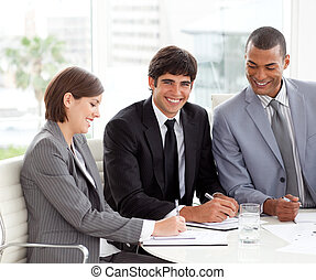 Attractive young businessman smiling at the camera in a meeting