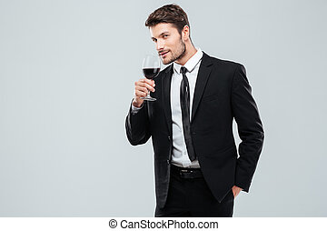 Attractive young businessman standing and drinking red wine