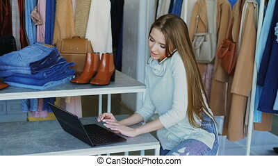Attractive young businesswoman is sitting and talking on...