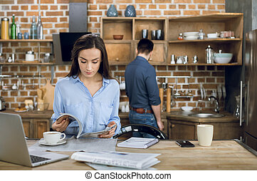 young businesswoman reading magazine while working at home