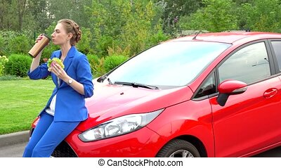 Attractive young businesswoman sits on front part of car...