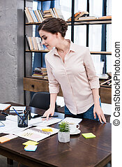 Attractive young businesswoman standing at table and working with papers