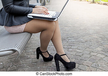 attractive young businesswoman working at computer sitting outdoors