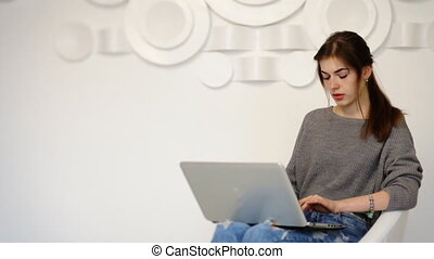 Attractive young businesswomanwearing grey sweater and blue jeans typing on her laptop at home.