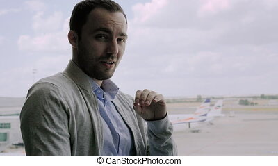 Attractive young caucasian businessman talking to camera explaining something with planes in the background.