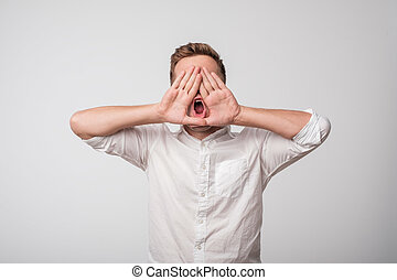 Attractive young caucasian man shouting.