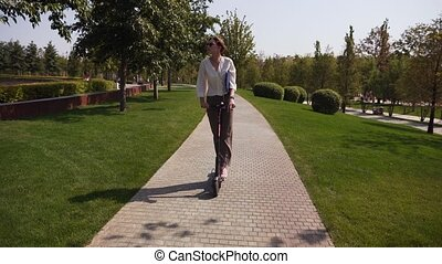 Attractive young caucasian woman controls a scooter, shot in motion. Ecological electric type of transport in nature and greenery