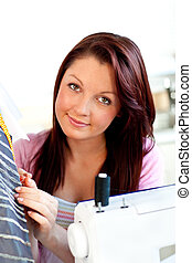 Attractive young caucasian woman sewing in the kitchen