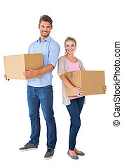 Attractive young couple carrying moving boxes