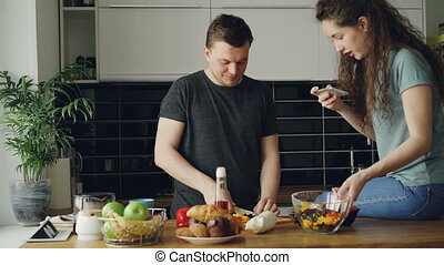 Attractive young couple cooking and chatting happily in the kitchen at home. Man cutting vegetables for salad and his girlfriend taking photos on smartphone camera for social media