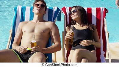 Attractive young couple enjoying a beer