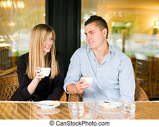 Attractive young couple enjoying beverage.