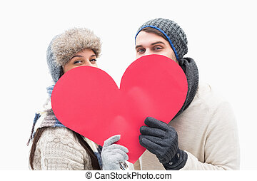 Attractive young couple in warm clothes holding red heart on...